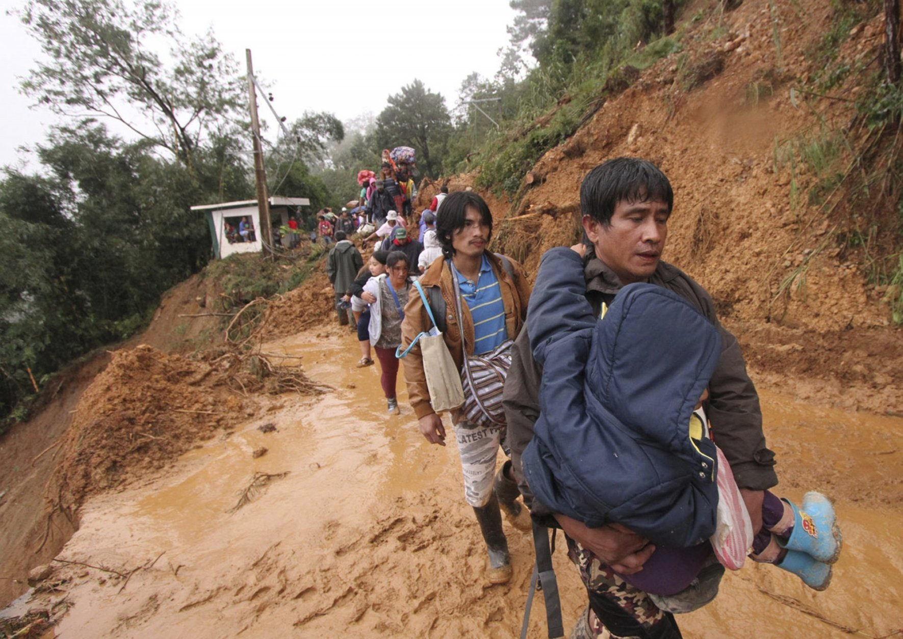 Residents and relatives of miners in Itogon township, Benguet province in the northern Philippines, carry their belongings as they evacuate to following landslides triggered by Typhoon Mangkhut burying an unknown number of miners and isolating the township Sunday, Sept. 16, 2018. Typhoon Mangkhut barreled into southern China on Sunday after lashing the northern Philippines with strong winds and heavy rain that left more than dozens dead from landslides and drownings. (AP Photo/Jayjay Landingin)