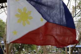 The Philippine flag flutters inside a camp as police clean fallen trees and debris after Typhoon Mangkhut barreled across Tuguegarao city in Cagayan province, northeastern Philippines on Sunday, Sept. 16, 2018. Typhoon Mangkhut roared toward densely populated Hong Kong and southern China on Sunday after ravaging across the northern Philippines with ferocious winds and heavy rain causing landslides and collapsed houses. (AP Photo/Aaron Favila)