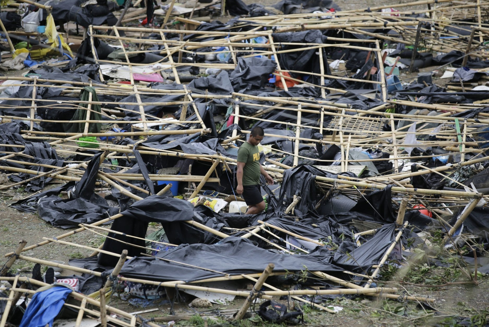 A policeman walks through makeshift tent shelters damaged by strong winds from Typhoon Mangkhut after it barreled across Tuguegarao city in Cagayan province, northeastern Philippines on Sunday, Sept. 16, 2018. Typhoon Mangkhut roared toward densely populated Hong Kong and southern China on Sunday after ravaging across the northern Philippines with ferocious winds and heavy rain causing landslides and collapsed houses. (AP Photo/Aaron Favila)