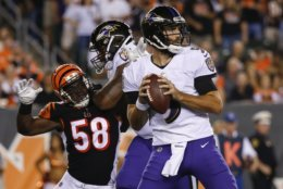 Baltimore Ravens quarterback Joe Flacco (5) looks to pass under pressure from Cincinnati Bengals defensive end Carl Lawson (58) in the first half of an NFL football game, Thursday, Sept. 13, 2018, in Cincinnati. (AP Photo/Frank Victores)