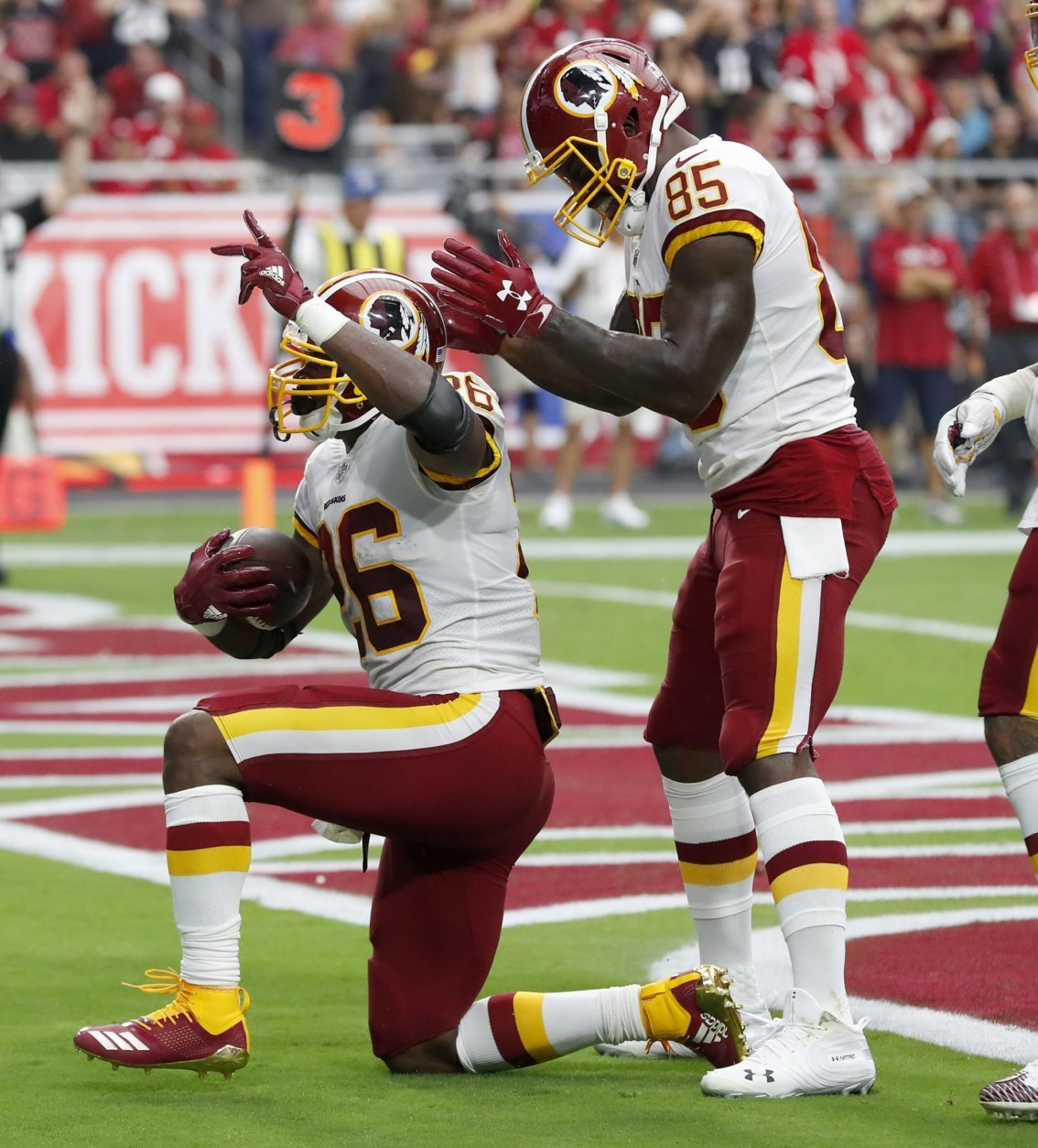 Washington Redskins running back Adrian Peterson (26) celebrates his touchdown against the Arizona Cardinals with tight end Vernon Davis (85) during the first half of an NFL football game, Sunday, Sept. 9, 2018, in Glendale, Ariz. (AP Photo/Rick Scuteri)