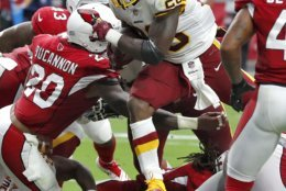 Washington Redskins running back Adrian Peterson (26) scores a touchdown as Arizona Cardinals linebacker Deone Bucannon (20) defends during the first half of an NFL football game, Sunday, Sept. 9, 2018, in Glendale, Ariz. (AP Photo/Rick Scuteri)