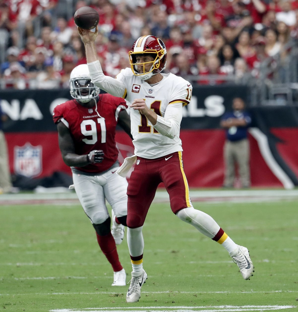 Washington Redskins quarterback Alex Smith (11) throws as Arizona Cardinals defensive end Benson Mayowa (91) pursues during the first half of an NFL football game, Sunday, Sept. 9, 2018, in Glendale, Ariz. (AP Photo/Rick Scuteri)