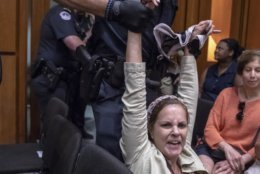 A protester disrupts the proceedings as President Donald Trump's Supreme Court nominee, Brett Kavanaugh, appears before the Senate Judiciary Committee for the second day of his confirmation hearing, on Capitol Hill in Washington, Wednesday, Sept. 5, 2018. (AP Photo/J. Scott Applewhite)