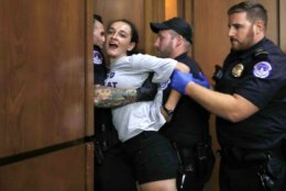 A protester is removed from the hearing room as President Donald Trump's Supreme Court nominee, Brett Kavanaugh testifies before the Senate Judiciary Committee on Capitol Hill in Washington, Wednesday, Sept. 5, 2018, for the second day of his confirmation hearing to replace retired Justice Anthony Kennedy. (AP Photo/Jacquelyn Martin)