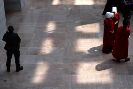 """A U.S. Capitol Police Officer stands near as protesters of Supreme Court nominee Brett Kavanaugh wear costumes from the show """"The Handmaid's Tale,"""" during his confirmation hearing with the Senate Judiciary Committee on Capitol Hill, Tuesday, Sept. 4, 2018, in Washington. (AP Photo/Jacquelyn Martin)"""