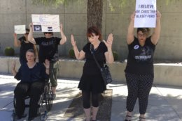 Lisa McAllister, left, Virginia Wisdom, center, and Karina Provost demonstrate in support of Christine Blasey Ford in Las Vegas on Thursday, Sept. 27, 2018. Nevada's Republican governor says the U.S. Senate should not cast a final vote on the U.S. Supreme Court nomination of Brett Kavanaugh without a full review of the allegations of sexual misconduct that have been made against the nominee. (AP Photo/Michelle L. Price)