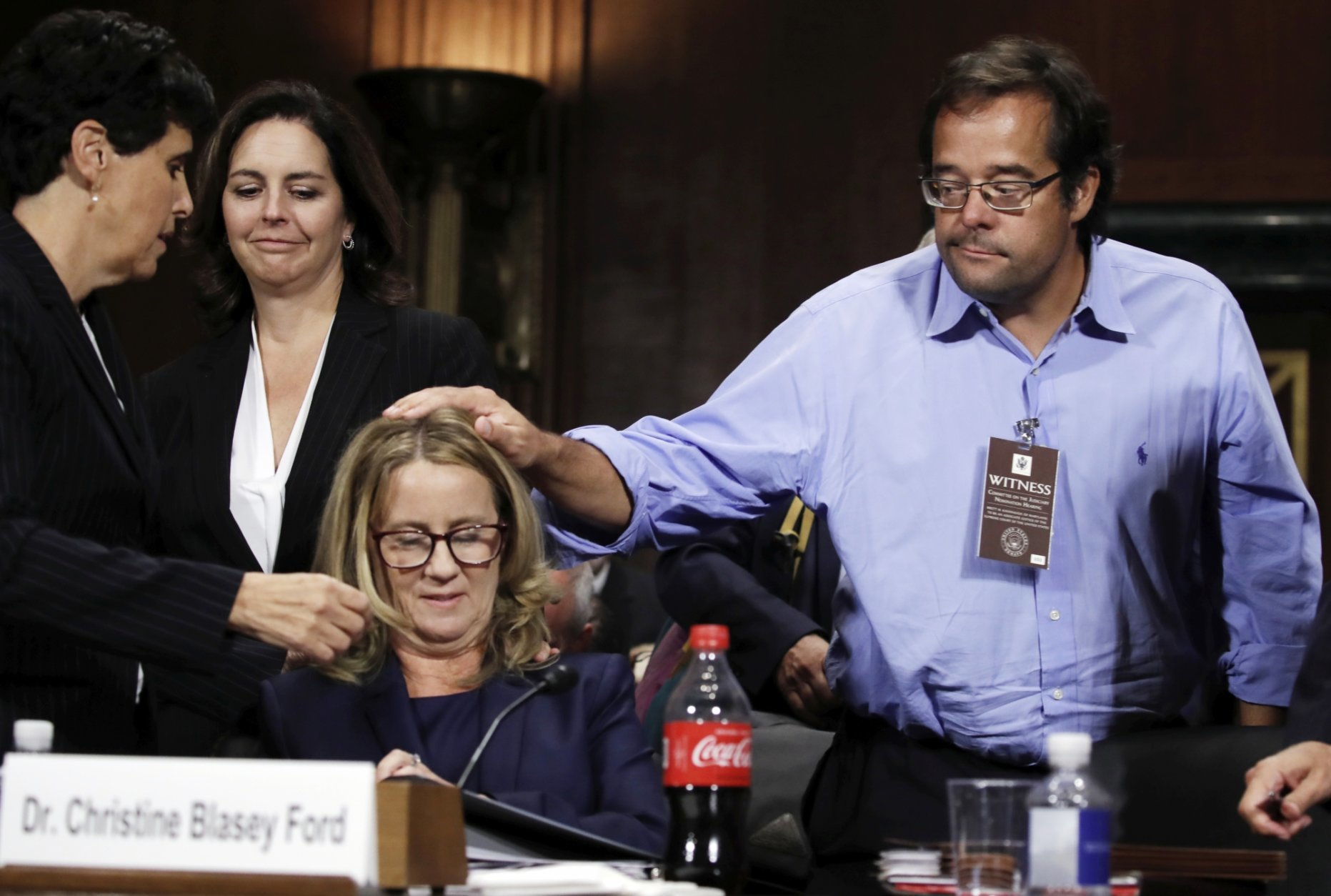 Christine Blasey Ford listens to her attorney Debra Katz, as Keith Kogner pats her on the head at the end of a hearing before the Senate Judiciary Committee on Capitol Hill Thursday, Sept. 27, 2018 in Washington. (Jim Bourg/Pool Photo via AP)