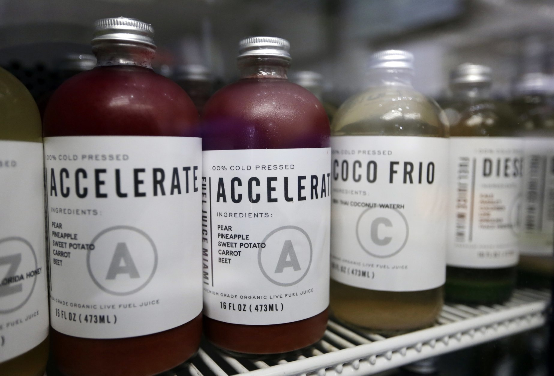 In this Tuesday, Aug. 14, 2018 photo, cold pressed juice pressed by Mendez Fuel is displayed at the Mendez Fuel convenience store in Miami. A new crop of niche stores aimed at millennials who can afford to pay more have completely overhauled store shelves, making gluten-free and organic products their staples, not just the side dish, along with compostable straws and on-demand delivery. (AP Photo/Lynne Sladky)