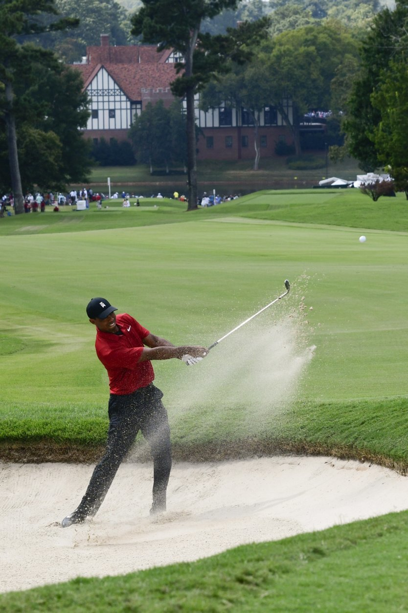 Tiger Woods hits out of the sand to the fifth green during the final round of the Tour Championship golf tournament Sunday, Sept. 23, 2018, in Atlanta. (AP Photo/John Amis)