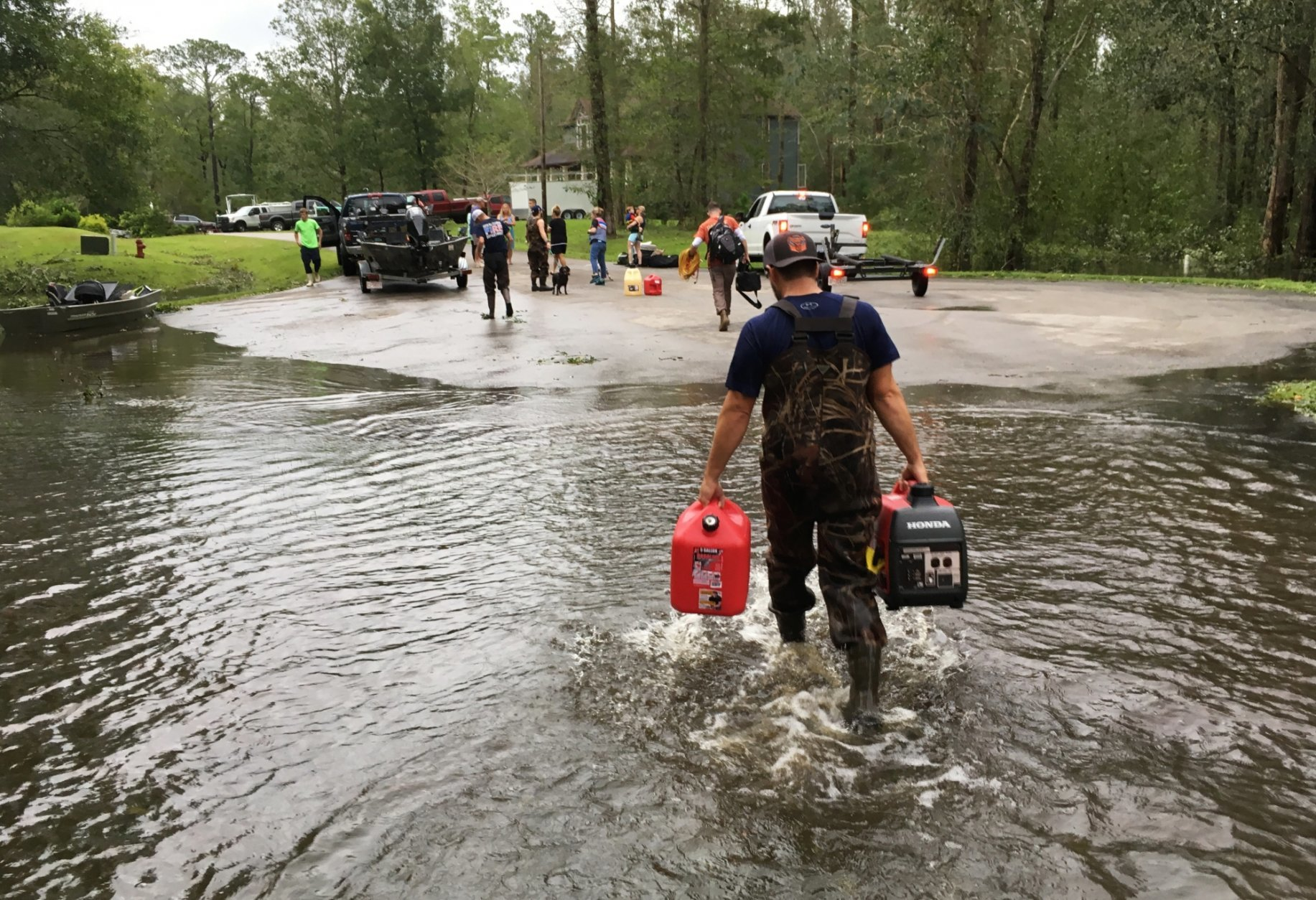 Kevin Knox carries gas and a generator after being rescued from his flooded neighborhood from the effects of Florence, now a tropical storm, in New Bern, N.C., on Saturday, Sept. 15, 2018. (AP Photo/Allen G. Breed)