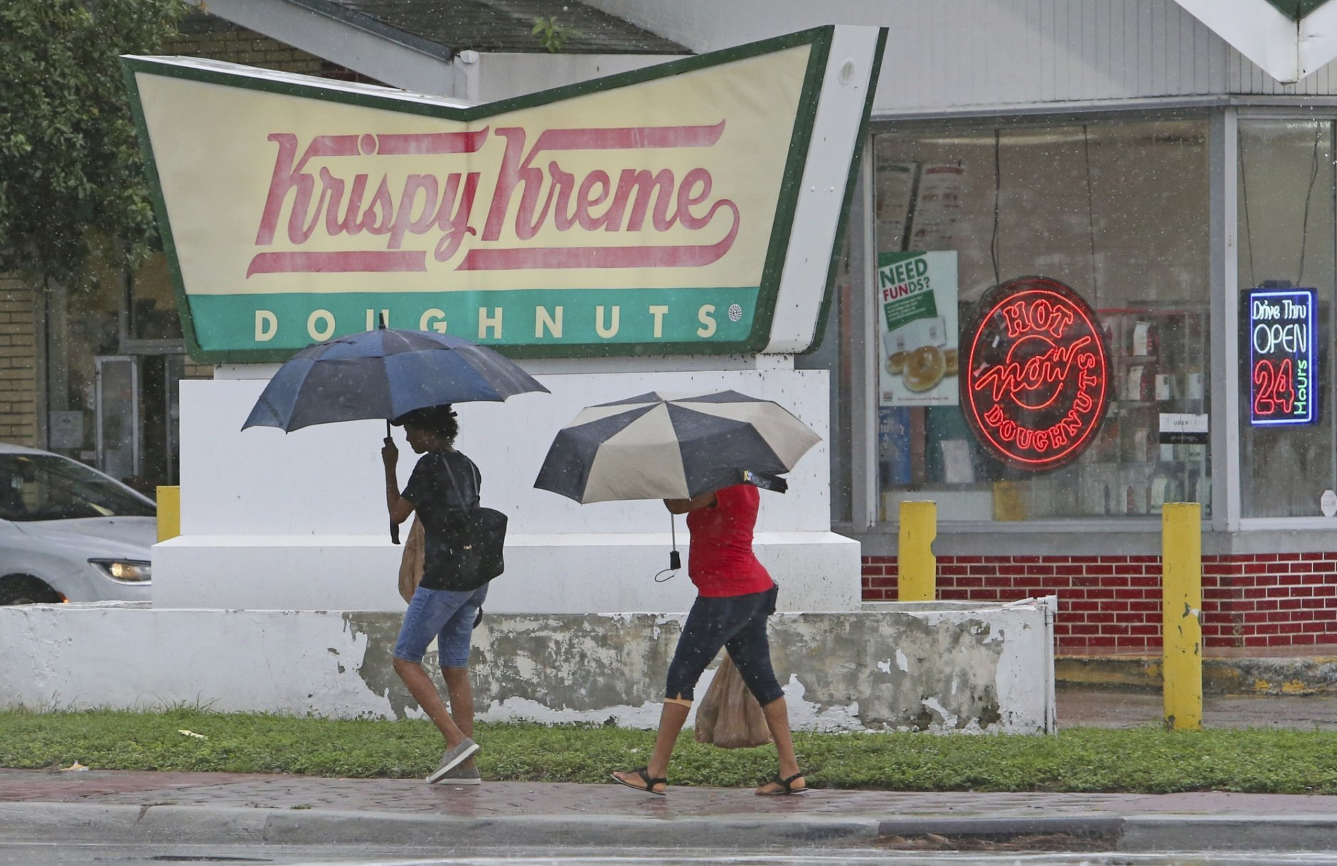 Two woman covered from the rain with umbrellas as they walk in Miami as Tropical Storm Gordon pass by South Florida with wind gust and heavy rainfall for the Labor Day holiday on Monday, Sept. 3, 2018. (David Santiago/Miami Herald via AP)