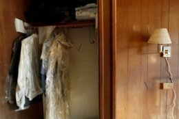 FILE- In this Wednesday, Sept. 19, 2018 file photo, wet clothing hangs in the closet of the Starlite Motel which was flooded in the aftermath of Hurricane Florence in Spring Lake, N.C. Renters fled in such a hurry that they left belongings still hanging in one closet, a suitcase in another and golf clubs on the floor. (AP Photo/David Goldman, File)