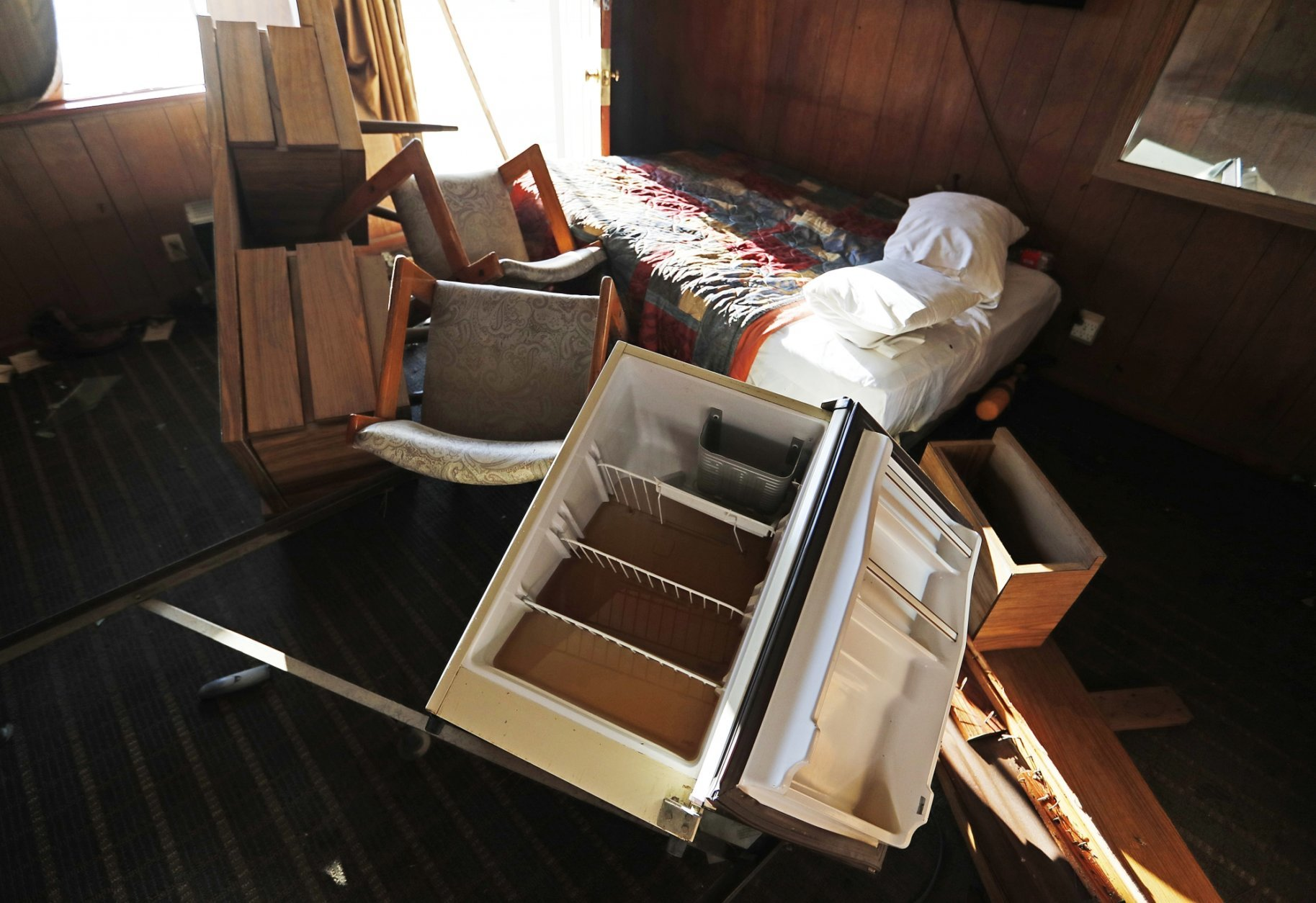 In this Wednesday, Sept. 19, 2018 photo, water sits in a refrigerator laying amongst furniture tossed about from flooding in the Starlite Motel in the aftermath of Hurricane Florence in Spring Lake, N.C. Florence washed away half the rooms at the Starlite Motel ripping away the livelihood of a family that bought it in recent months. (AP Photo/David Goldman)