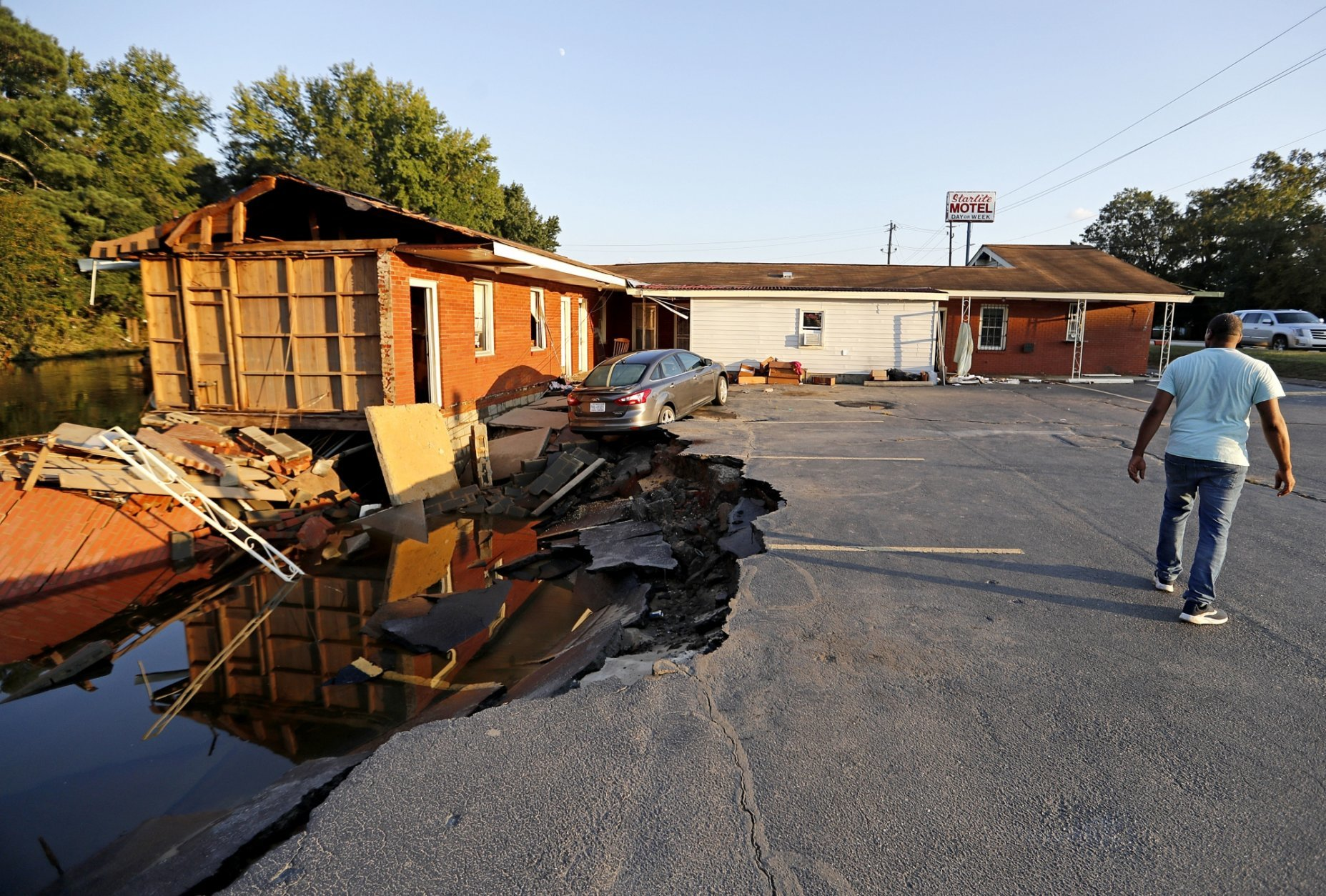In this Wednesday, Sept. 19, 2018 photo, part of the Starlite Motel is washed away in the aftermath of flooding from Hurricane Florence in Spring Lake, N.C. Florence washed away half the rooms at the Starlite Motel ripping away the livelihood of a family that bought it in recent months. (AP Photo/David Goldman)