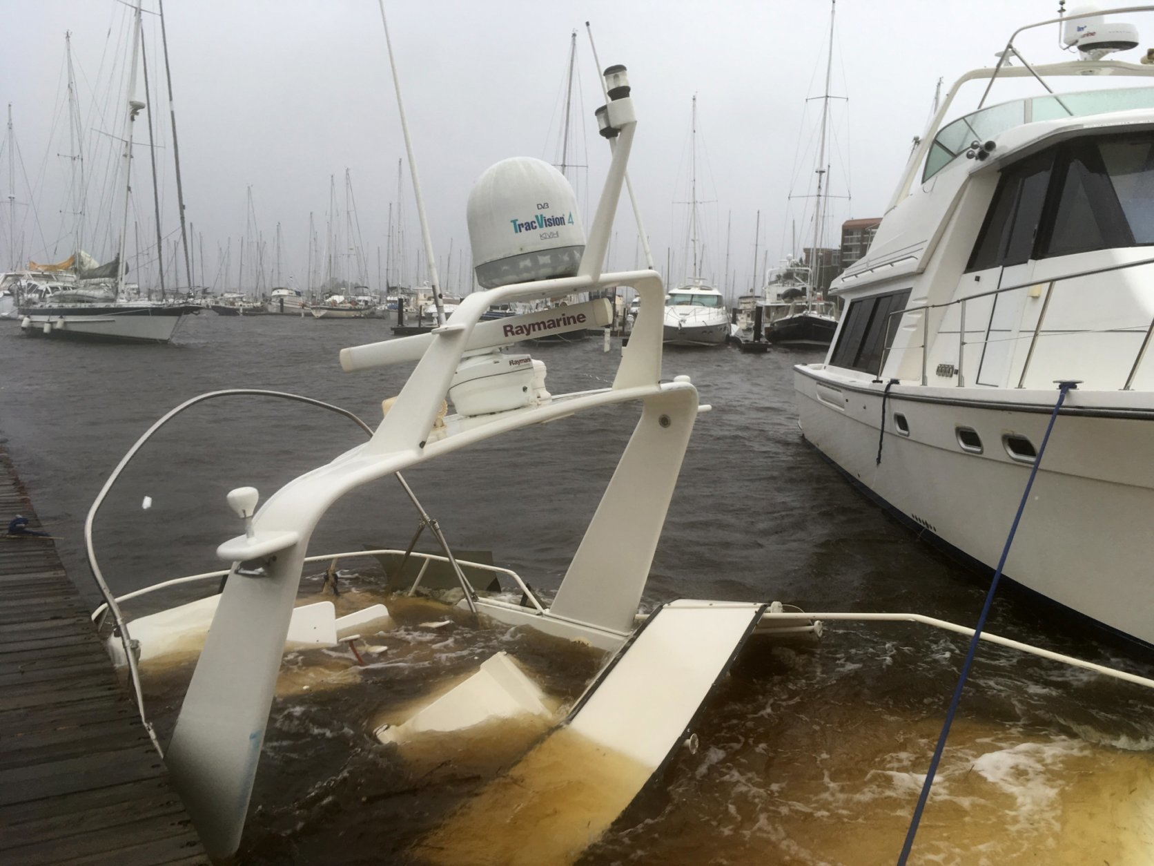 The mast of a sunken boat sits at a dock at the Grand View Marina in New Bern, N.C., on Friday, Sept. 14, 2018. Winds and rains from Hurricane Florence caused the Neuse River to swell, swamping the coastal city. (AP Photo/Allen G. Breed)