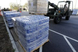 A member of the Civil Air Patrol brings in pallets of MREs and water to hand out at a distribution area in Wilmington, N.C. Tuesday, Sept. 18, 2018. (AP Photo/Chuck Burton)