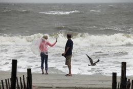 Lynn Williams, left, and Guy Covington of Hartsville watch the surf from Tropical Storm Florence as the storm pulled away from Myrtle Beach, N.C., on Saturday, Sept. 15, 2018. (Andrew Knapp/The Post And Courier via AP)