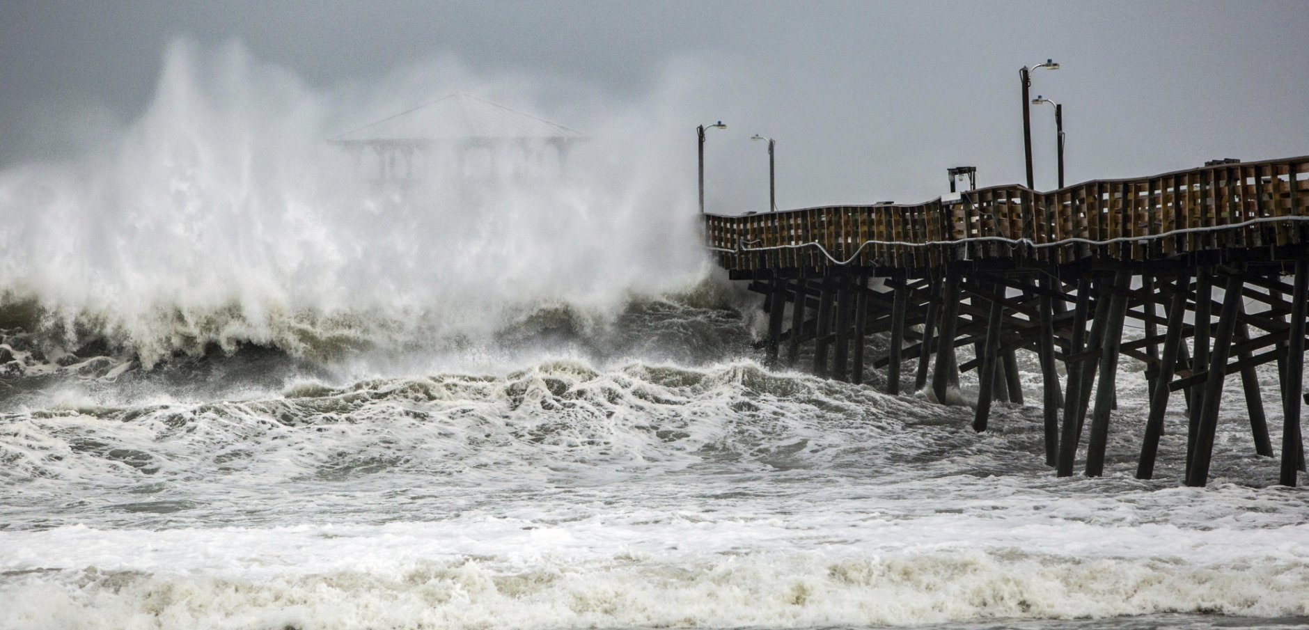 Waves slam the Oceana Pier & Pier House Restaurant in Atlantic Beach, N.C.,  Thursday, Sept. 13, 2018 as Hurricane Florence approaches the area.  (Travis Long /The News & Observer via AP)