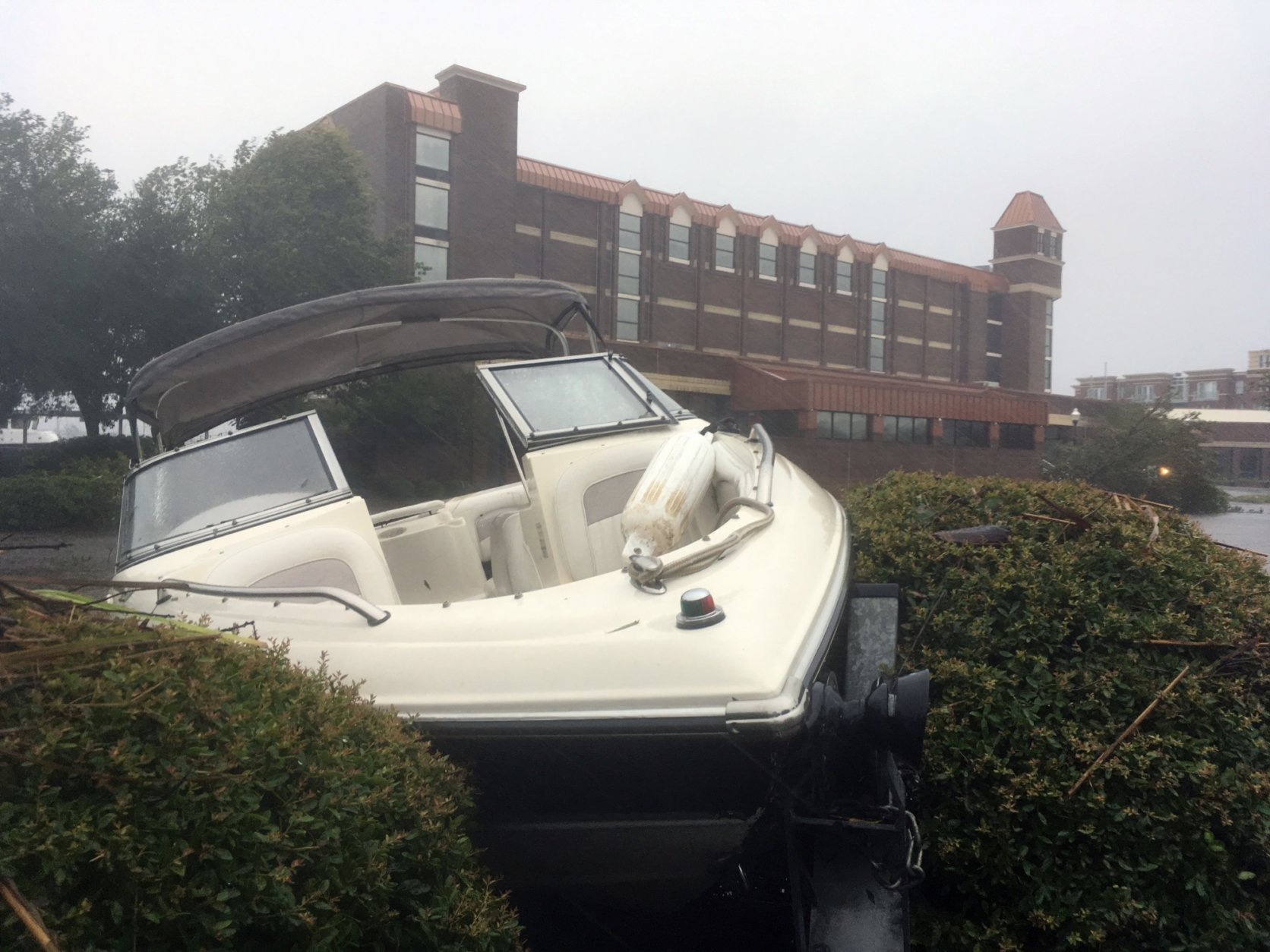 A speed boat sits wedged in bushes in the parking lot of a waterfront hotel in New Bern, N.C., on Friday, Sept. 14, 2018. Winds and rains from Hurricane Florence caused the Neuse River to swell, swamping the coastal city. (AP Photo/Allen G. Breed)
