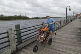FILE - In this Thursday, Sept. 13, 2018 file photo, a man jogs down the boardwalk by the Cape Fear River in downtown Wilmington, N.C., as Hurricane Florence threatens the coast. Record flooding is expected on Cape Fear River in the coming week, and signs of the coming flood are already apparent. The Cape Fear River is predicted to crest at 62 feet (nearly 19 meters) in Fayetteville on Tuesday, Sept. 18. (AP Photo/Chuck Burton, File)
