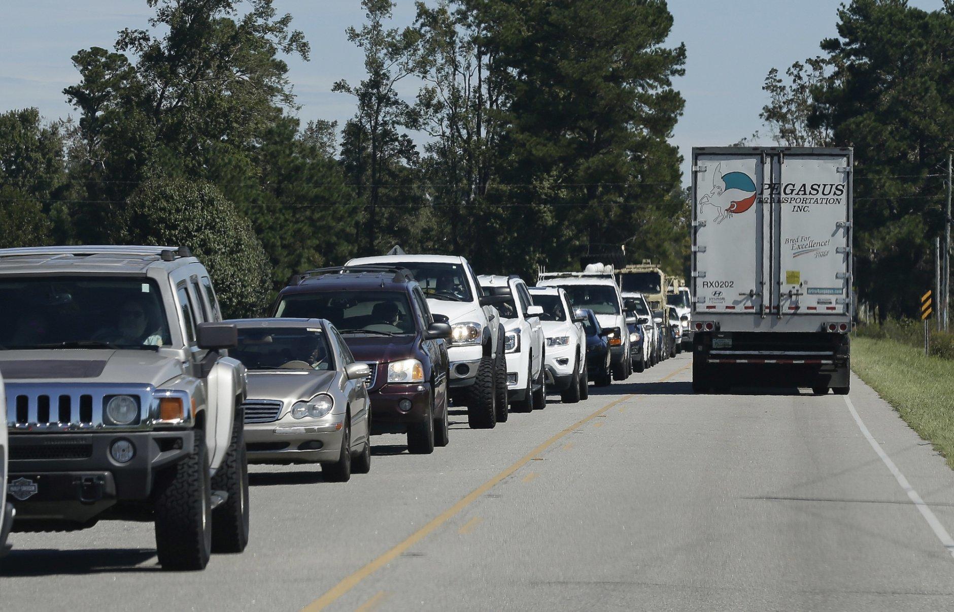 Vehicles are backed up along N.C. Highway 301 while attempting to navigate to Lumberton, N.C., Tuesday, Sept. 18, 2018 following flooding and road closures resulting from Hurricane Florence. (AP Photo/Gerry Broome)