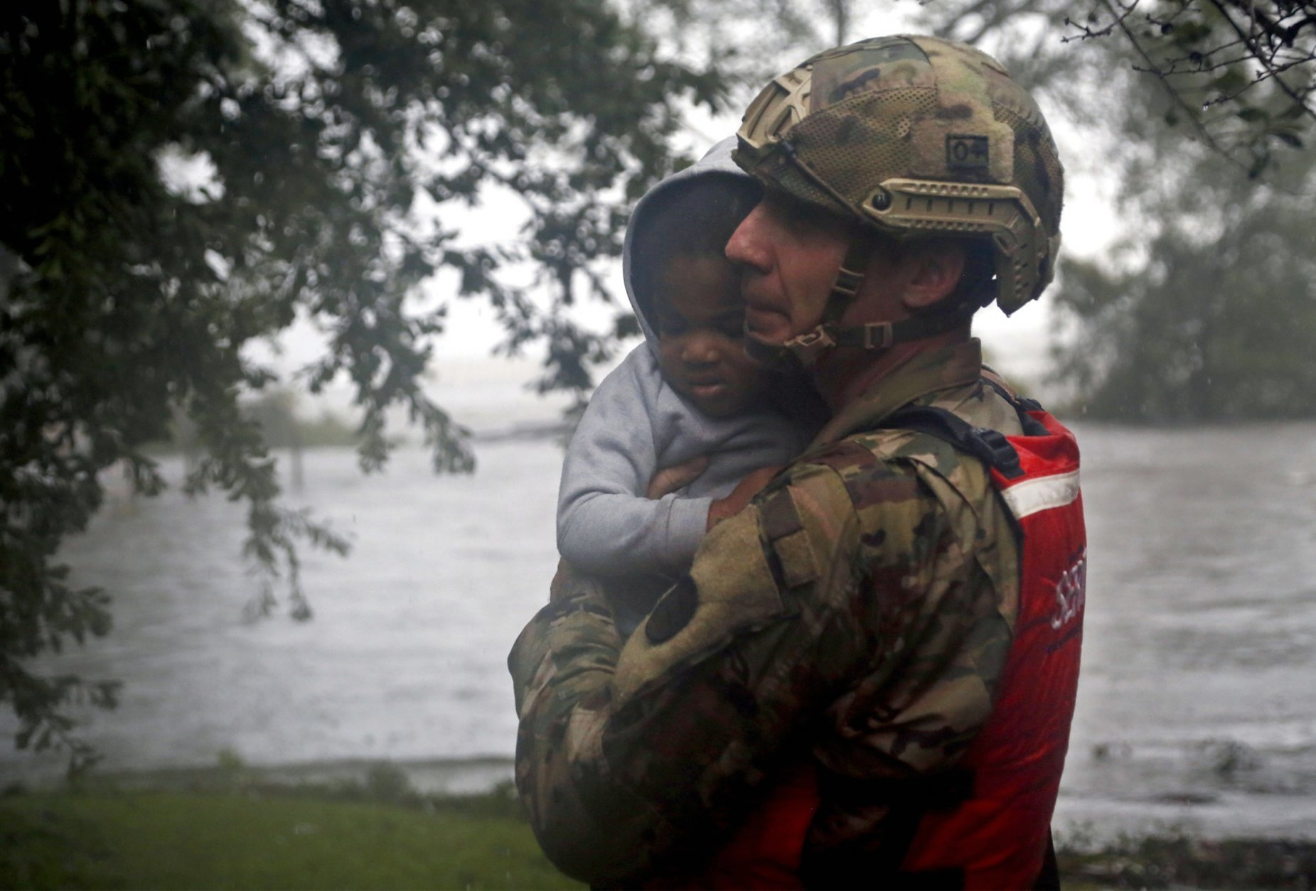 Rescue team member Sgt. Nick Muhar, from the North Carolina National Guard 1/120th battalion, evacuates a young child as the rising floodwaters from Hurricane Florence threatens his home in New Bern, N.C., on Friday, Sept. 14, 2018. (AP Photo/Chris Seward)
