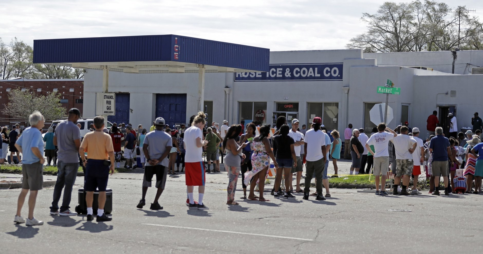 Customers line up outside Rose Ice and Coal Co. to purchase bags of ice in Wilmington, N.C. Tuesday, Sept. 18, 2018. (AP Photo/Chuck Burton)