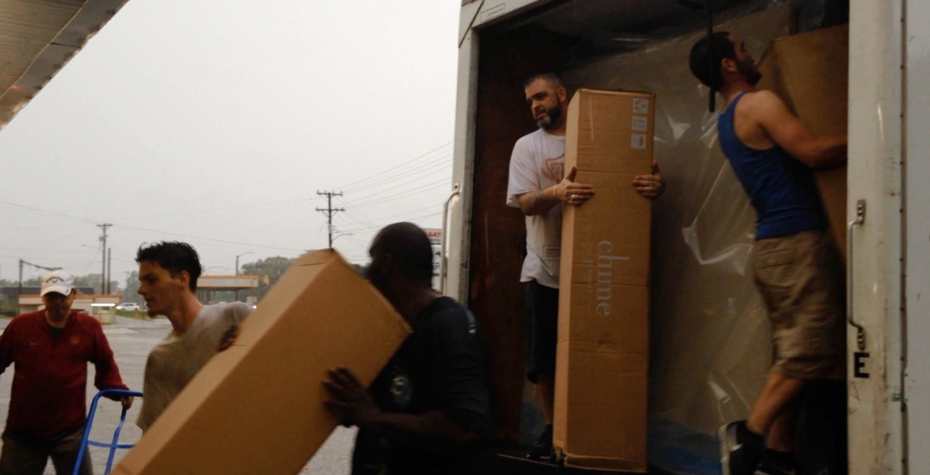 Rain-soaked furniture store workers load boxes into a truck, Saturday, Sept. 15, 2018, in Fayetteville, N.C., less than a mile from the Cape Fear River, which is set to crest at 62 feet early Tuesday. When John Rose who owns a furniture business heard about possible flooding, he quickly moved to have a crew empty more than 1,000 mattresses from a warehouse located in a low-lying strip mall threatened by the coming surge of water.  (AP Photo/Alex Derosier)