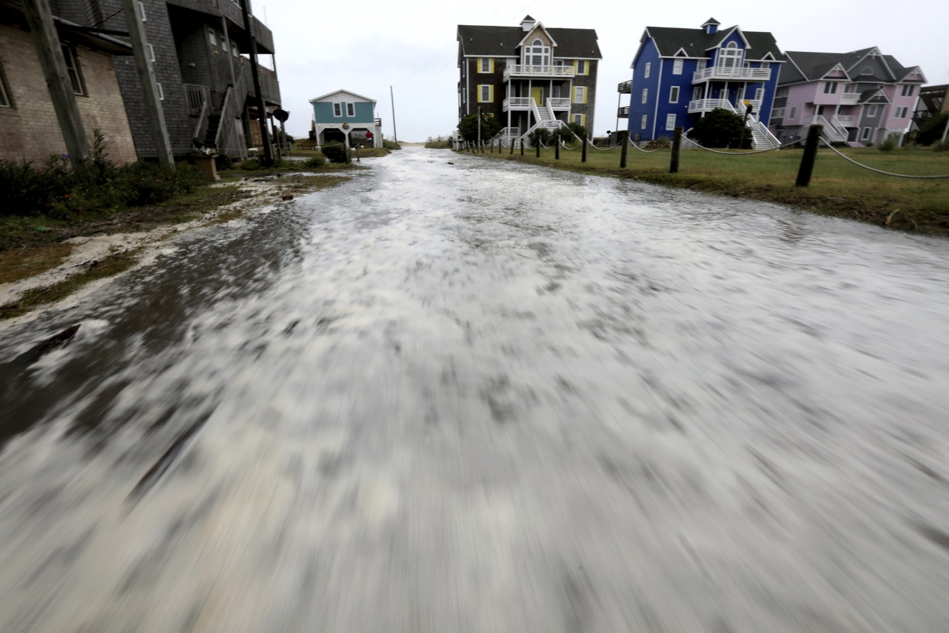 Ocean water rushes down Cape Hatteras Pier Drive in Frisco, N.C.,  on Hatteras Island as the effects of Hurricane Florence reach the area on Thursday, Sept. 13, 2018.  (Steve Earley /The Virginian-Pilot via AP)