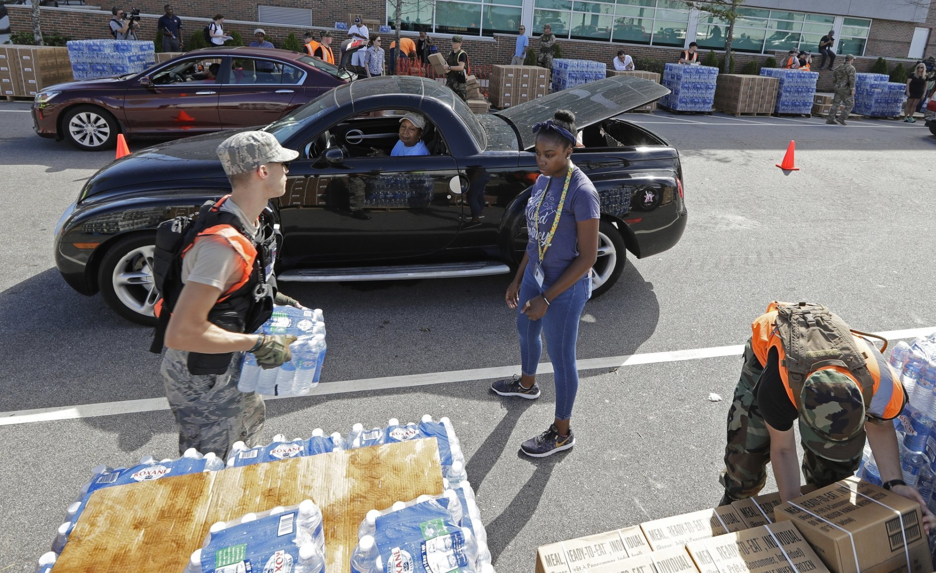 Members of the Civil Air Patrol load cars with MREs, (Meals Ready To Eat) water and tarps at distribution area in Wilmington, N.C. Tuesday, Sept. 18, 2018. (AP Photo/Chuck Burton)