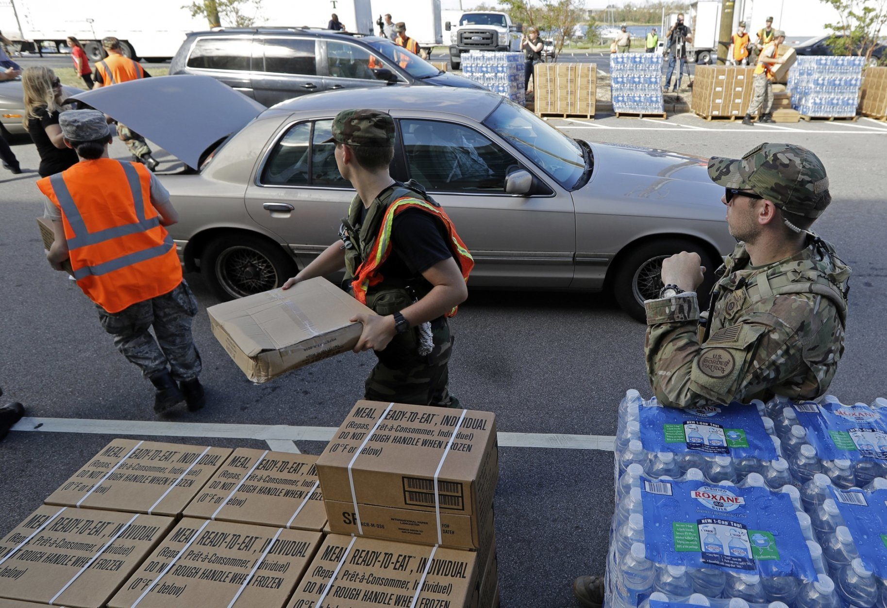 Members of the Civil Air Patrol load cars with MREs, water and tarps at distribution area in Wilmington, N.C. Tuesday, Sept. 18, 2018. (AP Photo/Chuck Burton)