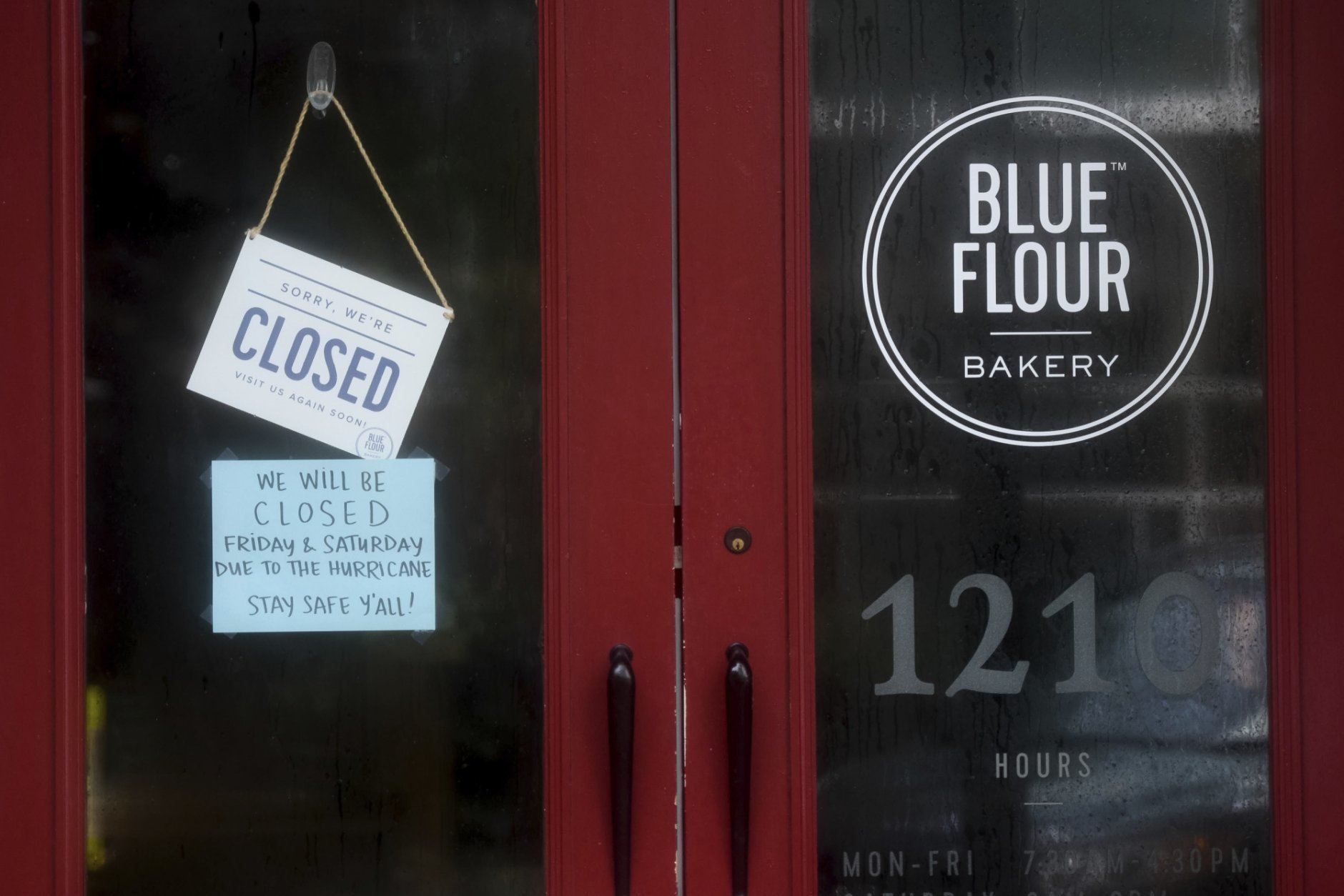 A closed sign hangs from the front door of the Blue Flour bakery on Main St. in Columbia, S.C. as the remnants of Hurricane Florence slowly move across the East Coast Saturday, Sept. 15, 2018. (AP Photo/Sean Rayford)