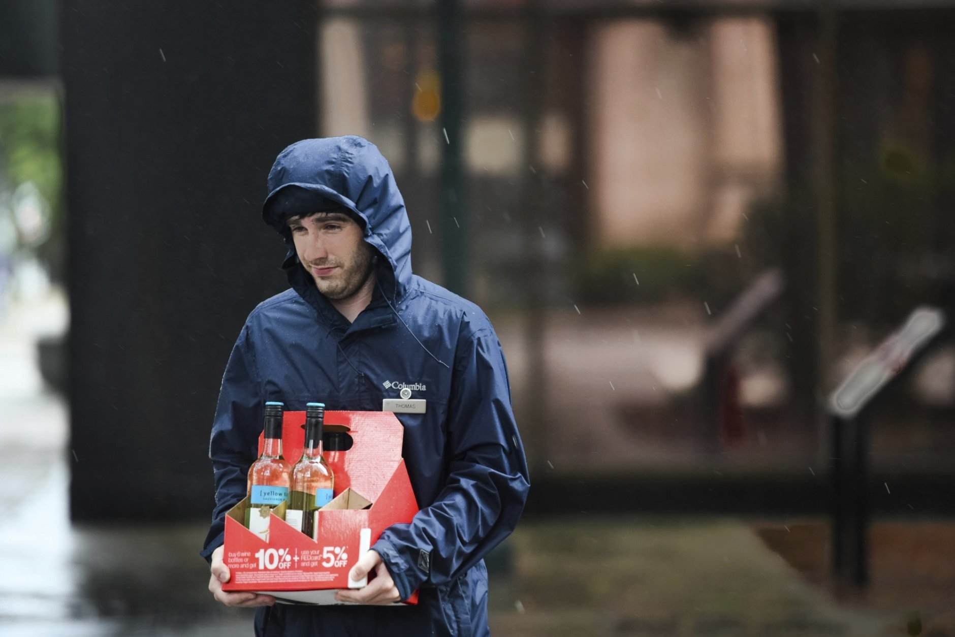 A young man carries bottles of wine down the sidewalk as the remnants of Hurricane Florence slowly move across the East Coast Saturday, Sept. 15, 2018, in Columbia, S.C. (AP Photo/Sean Rayford)