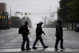 People cross a downtown street in Columbia, S.C. as the remnants of Hurricane Florence slowly move across the East Coast Saturday, Sept. 15, 2018. (AP Photo/Sean Rayford)