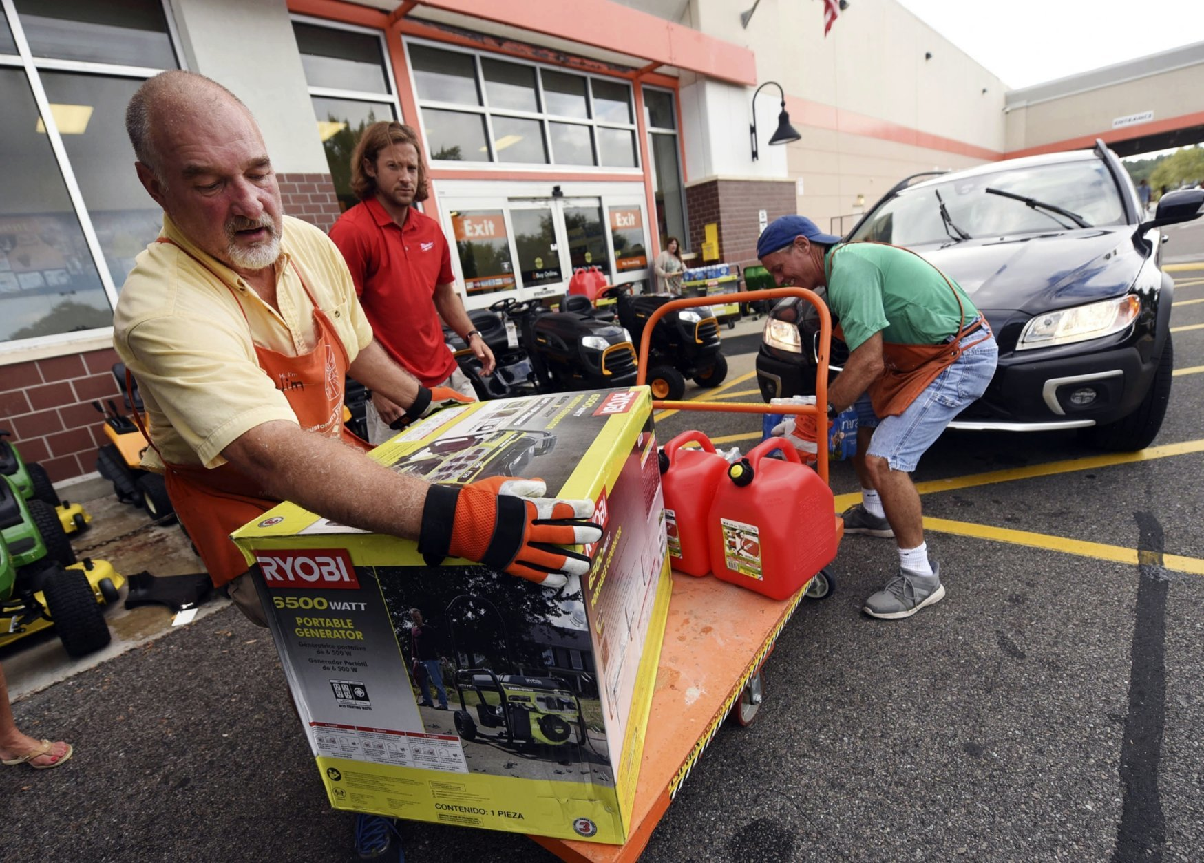 """FILE - In this Monday, Sept. 10, 2018 file photo, Jim Craig, David Burke and Chris Rayner load generators as people buy supplies at The Home Depot in Wilmington, N.C. """"It's a year-round thing for us,"""" said Margaret Smith, spokeswoman for Atlanta-based Home Depot. """"When it's hurricane season, we are operating 24 hours a day."""" (Ken Blevins/The Star-News via AP, File)"""