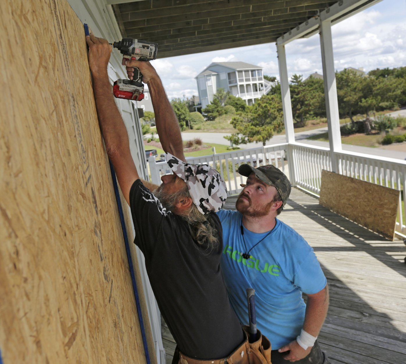 FILE - In this Wednesday, Sept. 12, 2018 file photo, Joe Gore, left, and Joshua Adcock prepare for Hurricane Florence as they board up windows on a home in Emerald Isle N.C. Before and after a hurricane, Ace is the place. And Home Depot, Lowe's, and many other hardware and building supply outlets. Not surprisingly, these companies plan for storms such as Hurricane Florence all year.  (AP Photo/Tom Copeland, File)