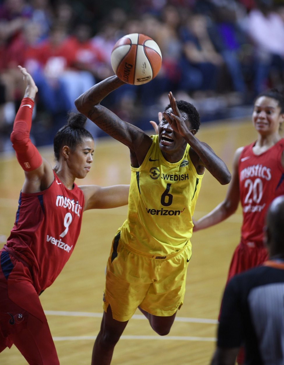 Seattle Storm forward Natasha Howard (6) goes to the basket against Washington Mystics guard Natasha Cloud (9) during the first half of Game 3 of the WNBA basketball finals, Wednesday, Sept. 12, 2018, in Fairfax, Va. Cloud was charged for a foul on the play. Also seen is Mystics guard Kristi Toliver (20). (AP Photo/Nick Wass)