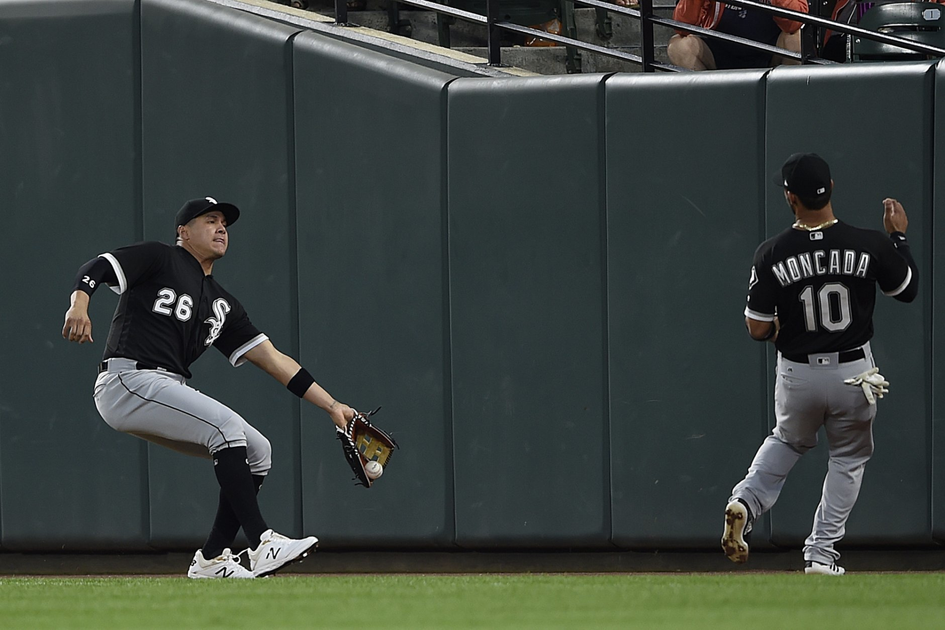 Chicago White Sox right fielder Avisail Garcia, left, is unable to hold onto a foul ball hit by Baltimore Orioles' Cedric Mullins in the first inning of a baseball game, Saturday, Sept. 15, 2018, in Baltimore. (AP Photo/Gail Burton)