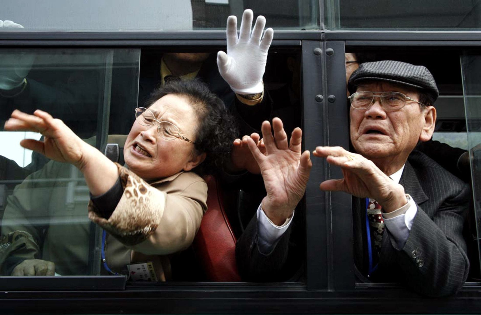 South Korean visitors in a bus wave to their North Korean relatives before they return to South Korea after the 13th Separated Family Reunion Meeting at Diamond Mountain in North Korea, Wednesday, March 22, 2006. About 150 South Koreans began a three-day reunion program at North Korea's Diamond Mountain resort on Monday, meeting with their North Korean relatives for the first time in more than half a century.(AP Photo/Munhwa Ilbo, Lim Jung-jyun, Korea Pool)  **KOREA OUT**