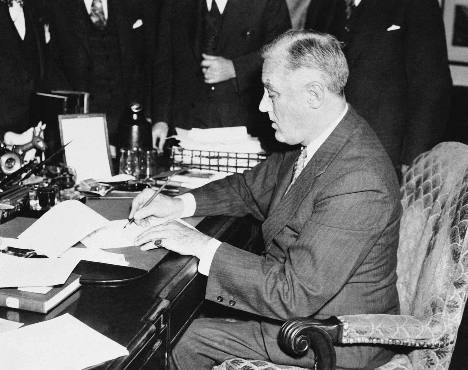 President Franklin Roosevelt is shown signing the neutrality bill in the White House, Washington on Nov. 4, 1939 making  law this bill which opens American markets to belligerent cash-and-carry purchasers.   The chief executive signed the bill before a gathering of congressional leaders and cabinet members - including Cordell Hull, Secretary of State. Only Roosevelt is shown in image. (AP Photo)