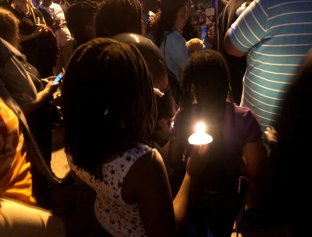 Neighbors lit candles and released balloons during a vigil, Thursday, Sept. 13, 2018, for slain teenager TaQuan Pinkney. (WTOP/Mike Murillo)