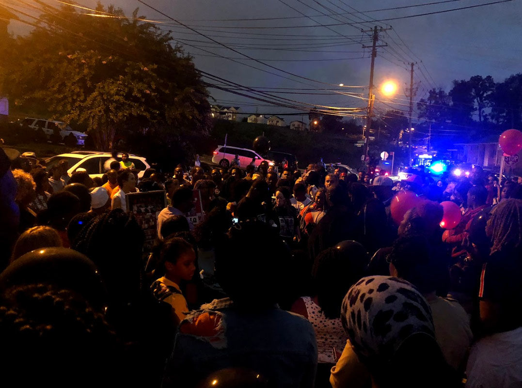 Holding candles, and with balloons, the community gathers on Thursday, Sept. 13, 2018, at the site where 18-year-old TaQuan Pinkney was gunned down. (WTOP/Mike Murillo)