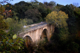 An abandoned, three-arch bridge towers over the Monocacy River in Maryland between Frederick and Linganore. The bridge was constructed in 1942 and was closed in 1985. (WTOP/Dave Dildine)