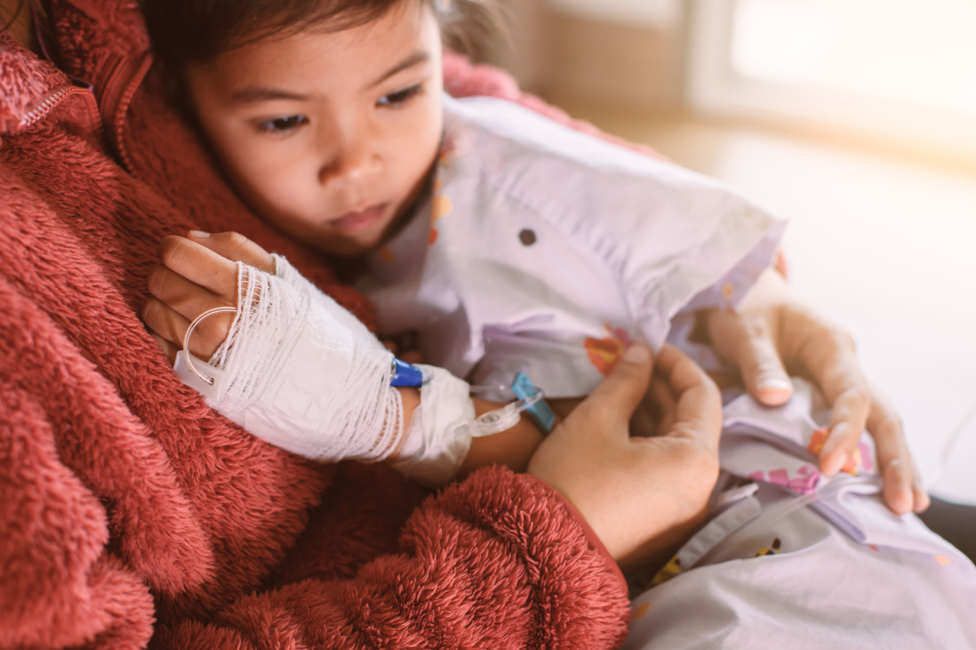 Sick asian little child girl who have IV solution bandaged hugging her mother with love in the hospital