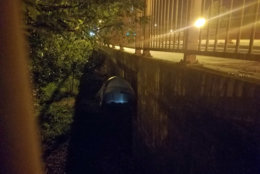 A light shines in a tent under the K Street Bridge. (WTOP/Will Vitka)