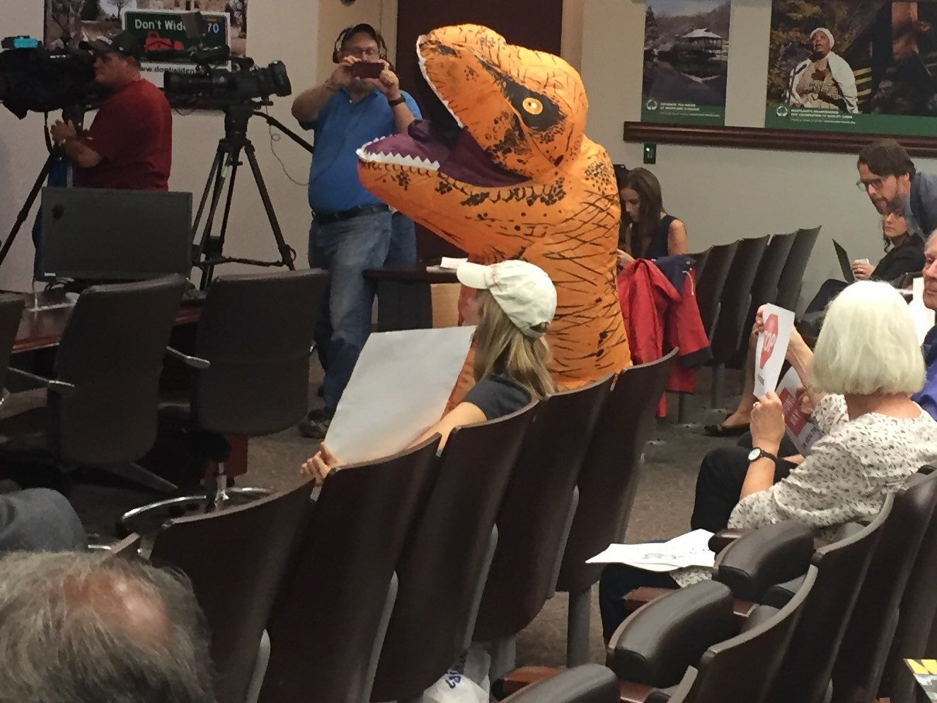 A person dressed as a dinosaur attends a public meeting on the widening of interstates 270 and 495 in Montgomery County on Thursday, Oct. 11, 2018. (WTOP/Mike Murillo)