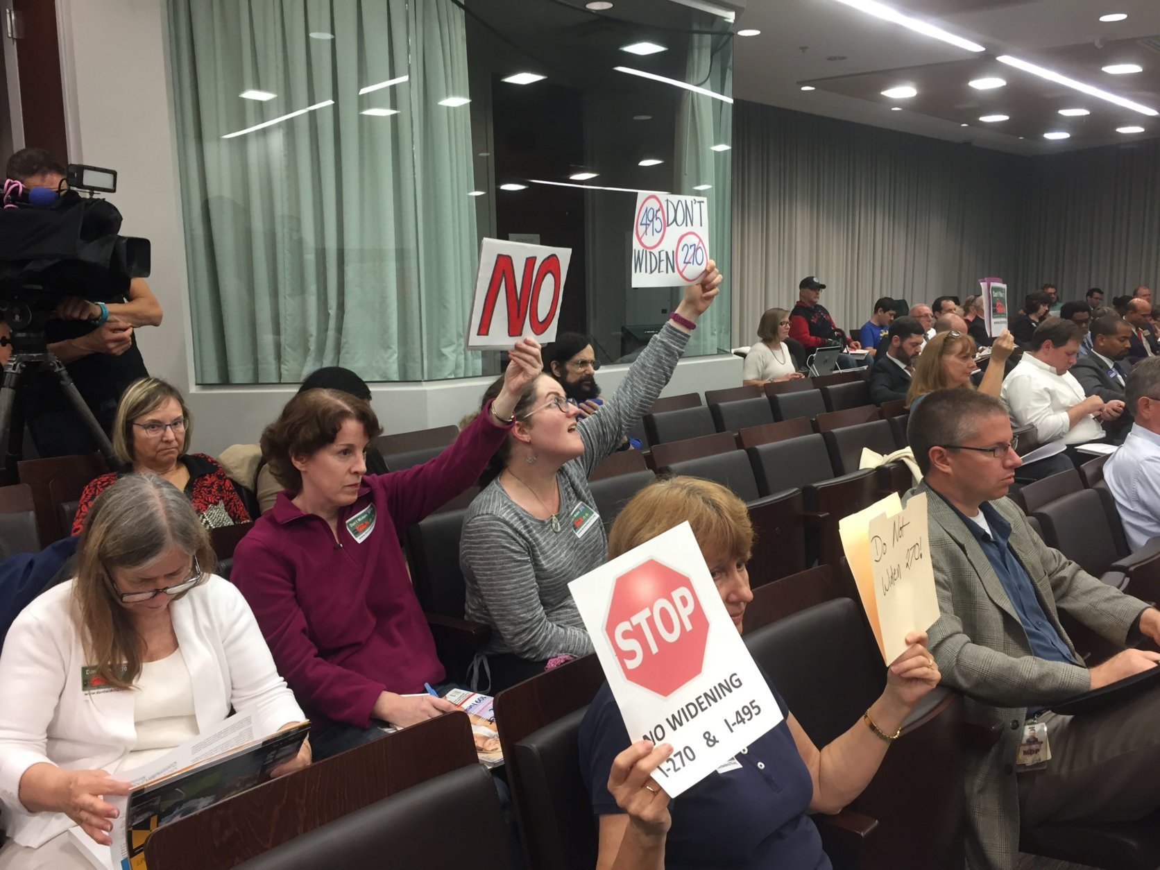 "Residents holding signs which read, ""Don't widen 270 & 495"" attended a public meeting Thursday, Oct. 11, 2018. (WTOP/Mike Murillo)"