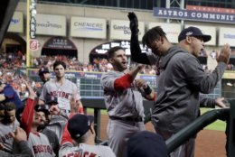 Boston Red Sox's Rafael Devers celebrates in the dugout after his three-run home run against the Houston Astros during the sixth inning in Game 5 of a baseball American League Championship Series on Thursday, Oct. 18, 2018, in Houston. (AP Photo/David J. Phillip)