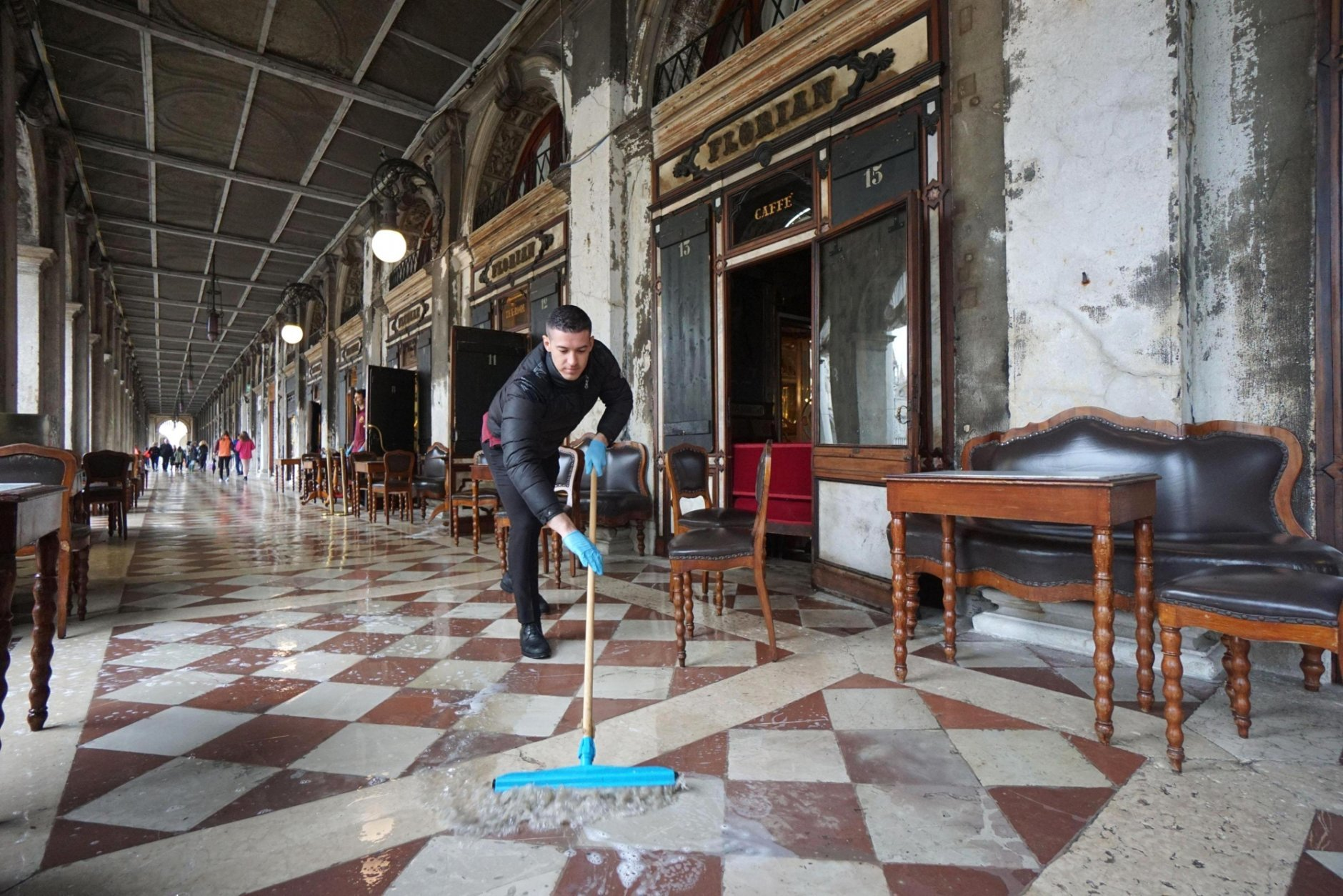 A man brushes away floodwater outside the historic Caffe Florian, in San Marco Square, in Venice, Italy, Tuesday, Oct.30 2018. High winds created an exceptional tide in Venice on Monday, covering three-quarters of the city for the first time in a decade. Water levels were forecast Tuesday at 110 centimeters (43.3 inches), flooding 12 percent of the famed lagoon city. (Andrea Merola/ANSA via AP)